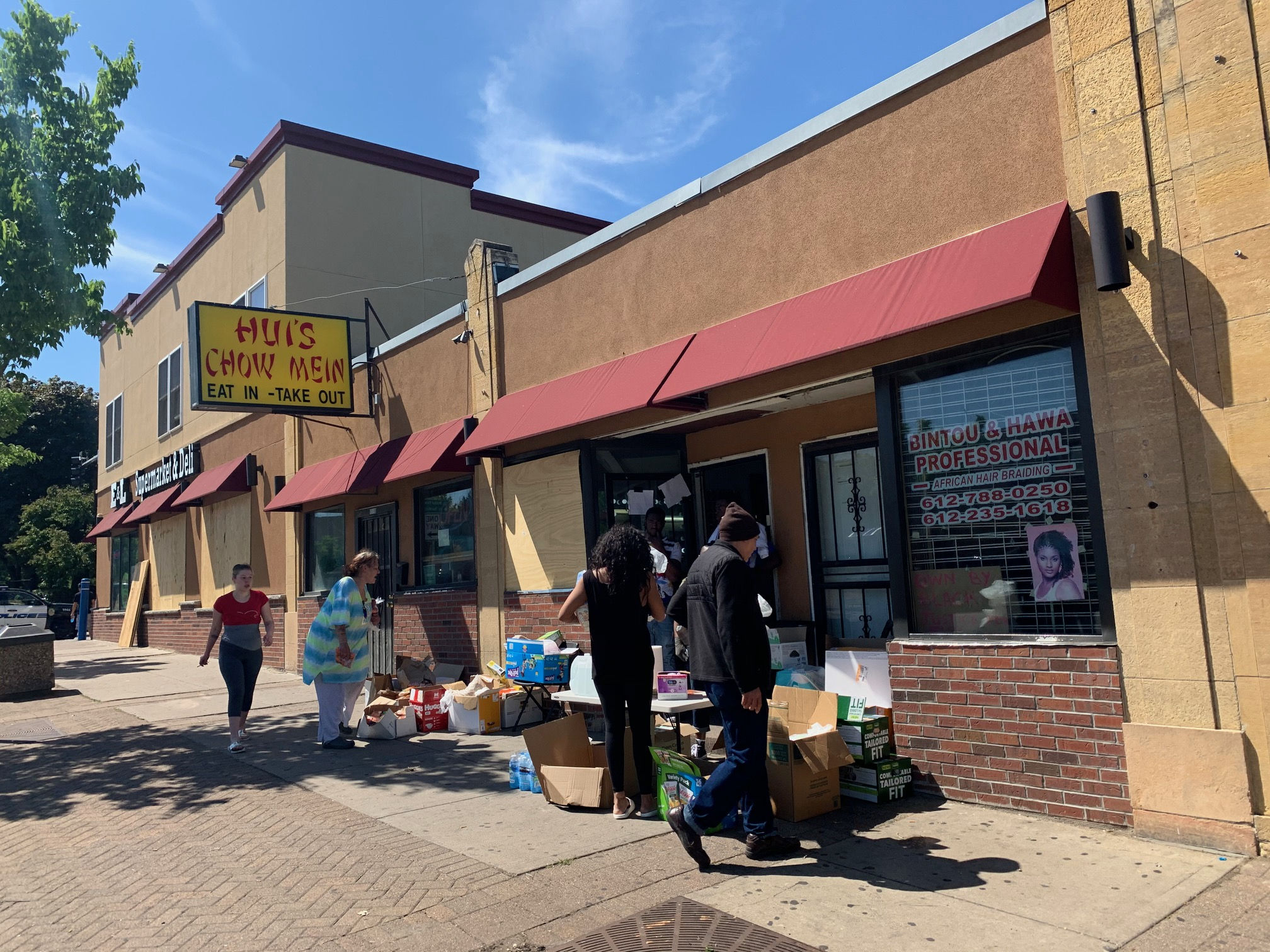 Barbers and volunteers give away donated groceries and essentials in front of FAME Hair Studio. Groceries are arranged haphazardly on the sidewalk while people peruse items.