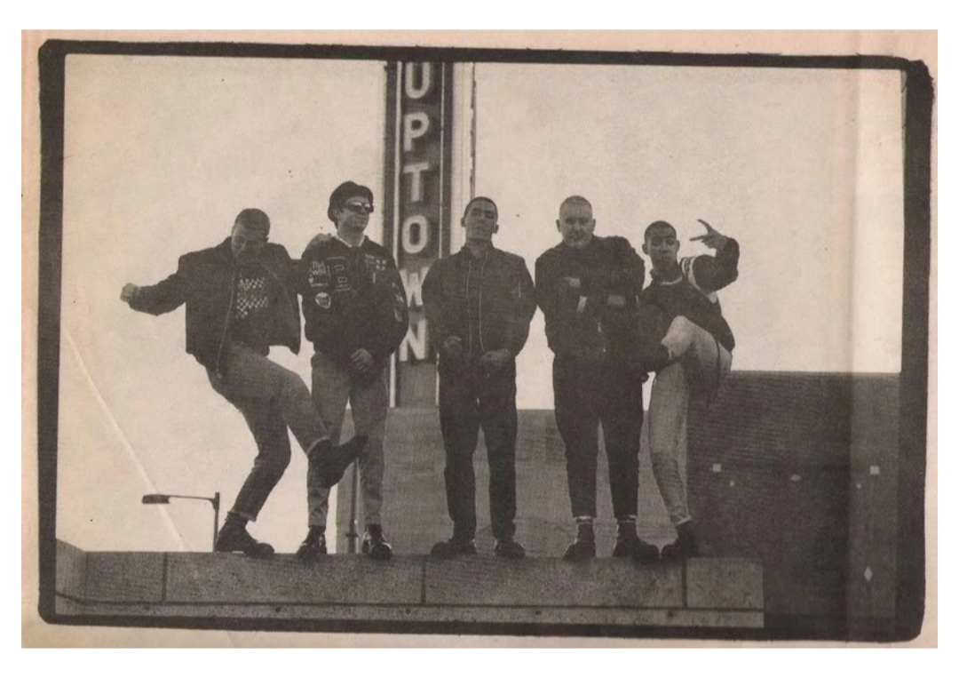 Five members of the The Baldies stand on a rooftop against the backdrop of the Uptown Theater marquee in Minneapolis, circa 1988.