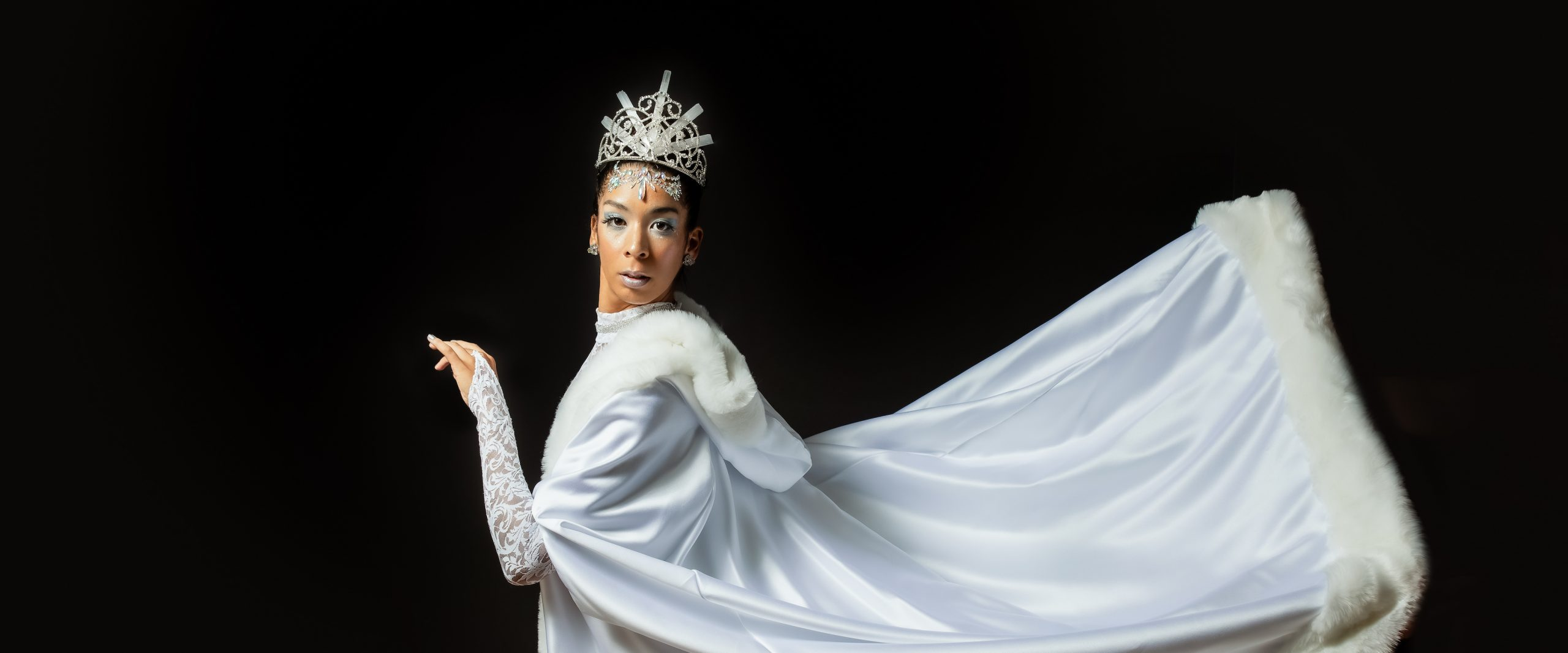 Snow Queen with Tiara looks over her left shoulder while her giant white cape suspends behind her