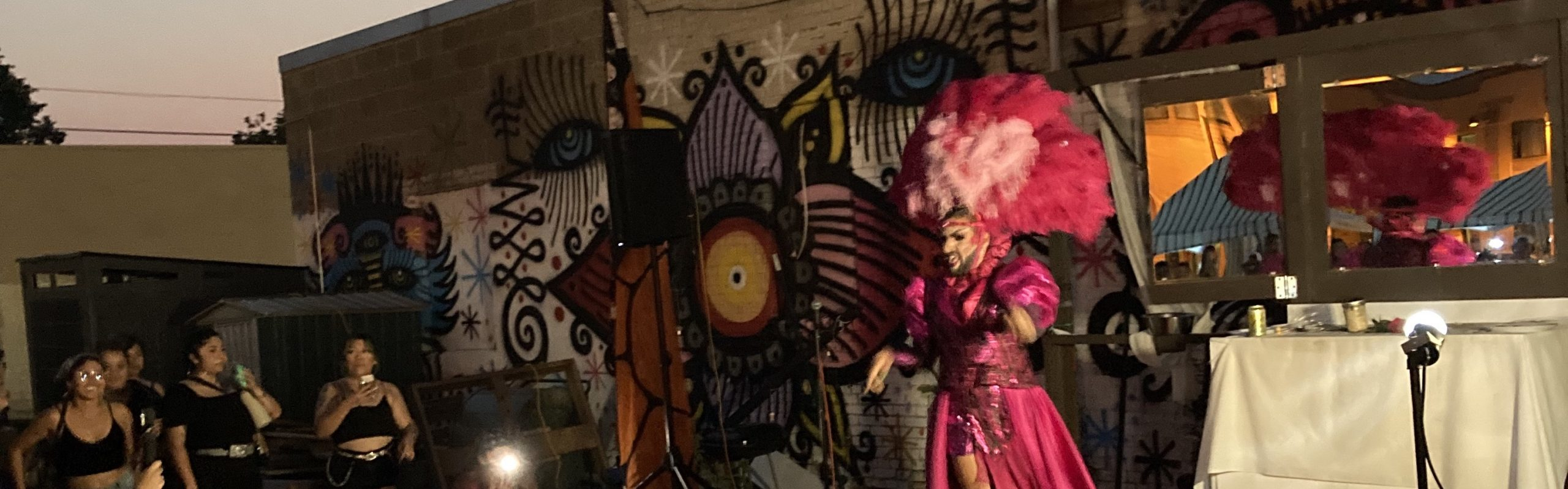 Dona Pepa dons a feather headdress and cape will on-stage at an outdoor stage at Lake Street and Chicago in Minneapolis.